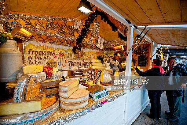 Christmas Market in Paris. Couple tasting Cheese.