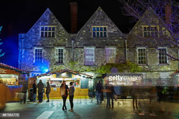 christmas market stalls in the grounds of winchester cathedral - winchester hampshire stock photos and pictures