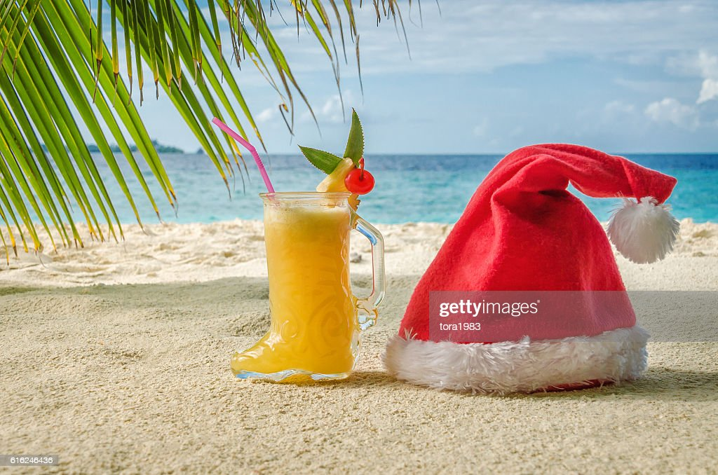 Christmas objects on the beach under a palm hat : Stock Photo