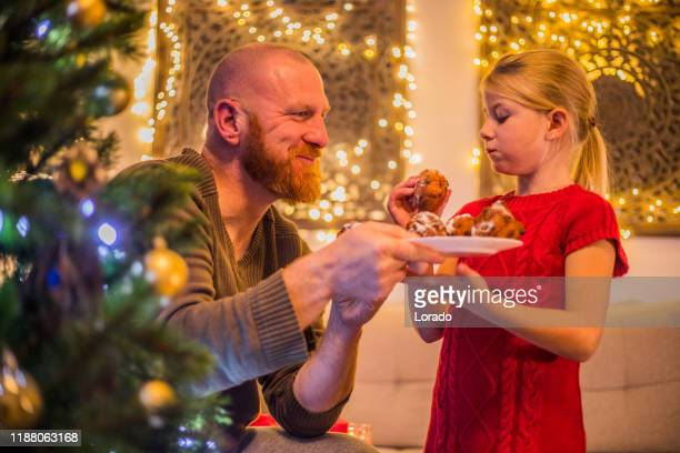 kerst oliebollen voor vader en dochter in xmas home - oliebol stockfoto's en -beelden