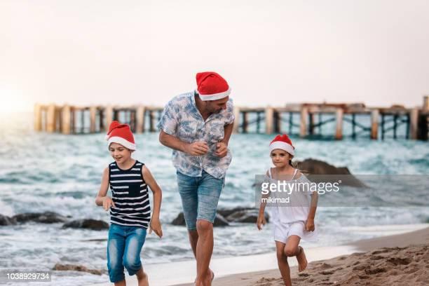 ビーチでのクリスマス。サンタの帽子と家族。父と子。