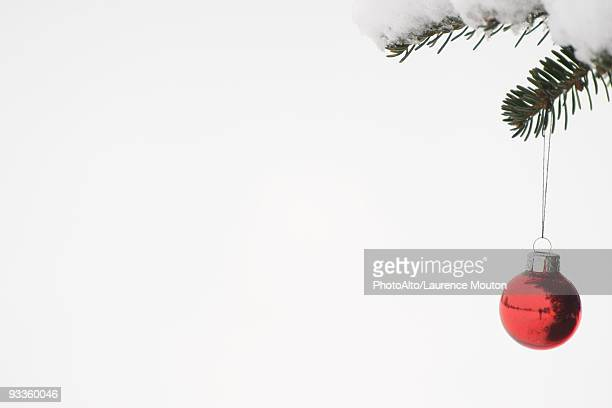 Christmas ornament hanging from snow-covered branch