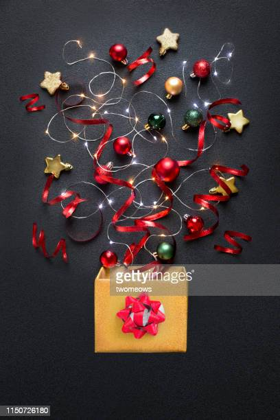 christmas ornaments and confetti bursting out from a gift box. - christmas still life stock pictures, royalty-free photos & images