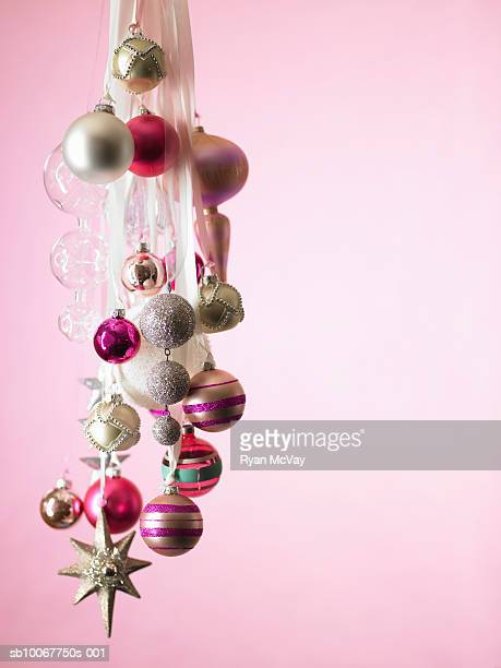 Christmas ornaments hanging against pink background