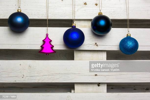 Christmas Ornaments Hanging Against White Wooden Fence
