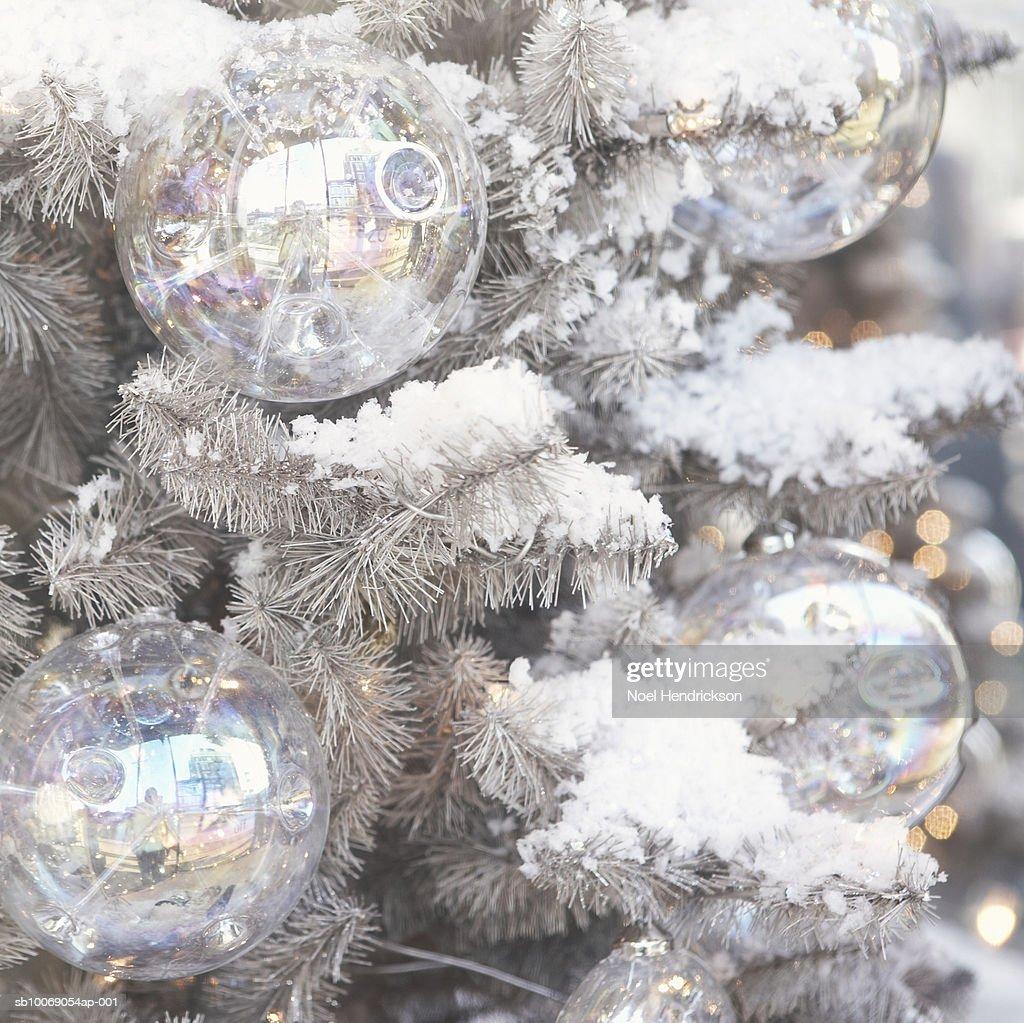 Christmas ornaments hanging on snowy tree : Stockfoto