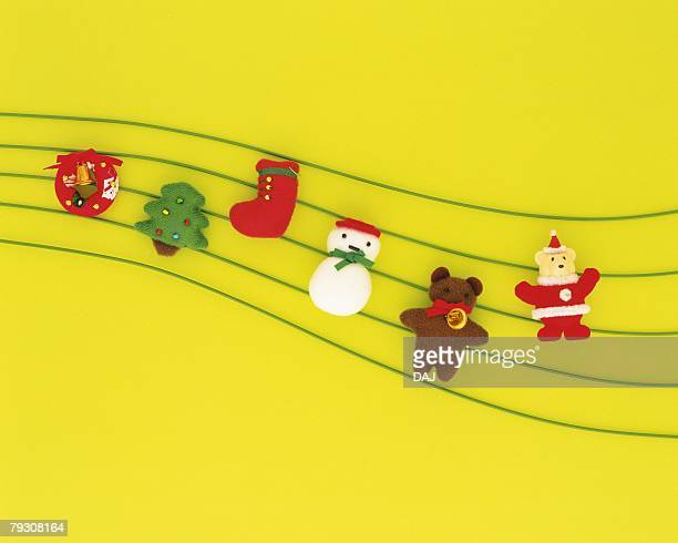 Christmas ornaments on lines, yellow background, high angle view
