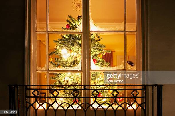 Christmas ornaments on tree behind window
