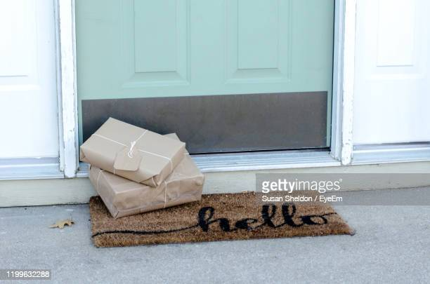 christmas packages waiting on the doorstep wrapped in brown paper and tied with string - gift stock pictures, royalty-free photos & images
