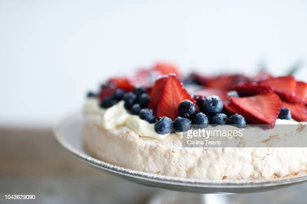 christmas pavlova wreath with fresh berries on a glass cake stand - christmas cake stock photos and pictures