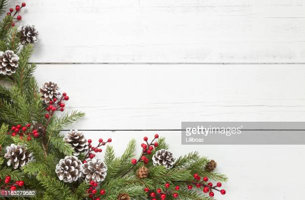christmas pine garland border on an old white wood background - christmas garland stock pictures, royalty-free photos & images