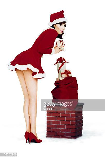 Christmas Pin-Up Girl Near Chimney Roof with Gifts
