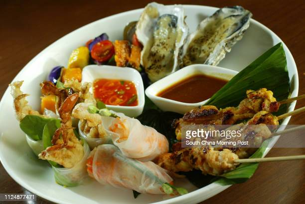 Christmas plate baked fresh oyster green cononut curry soft shell crab roll avocado and ginger rock lobster skewer and chicken satay in banana leaf...