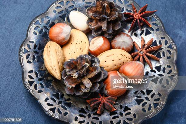 Christmas plate with nuts, spices and cedar cone
