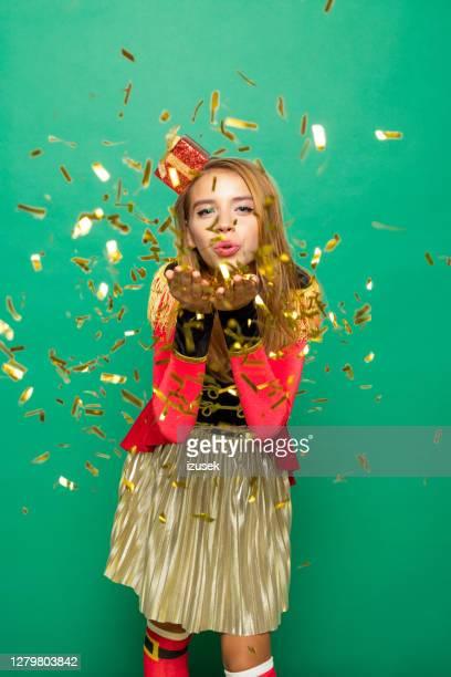 weihnachtsporträt von überraschten teenager-mädchen blasen konfetti - izusek stock-fotos und bilder