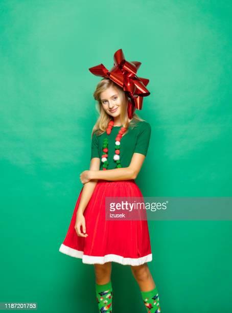 weihnachtsporträt von teenager-mädchen vor grünem hintergrund - izusek stock-fotos und bilder