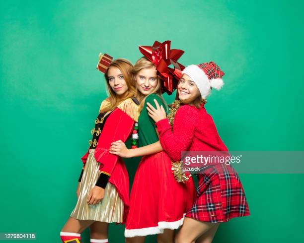 christmas portrait of three confident teenage girls - izusek stock pictures, royalty-free photos & images