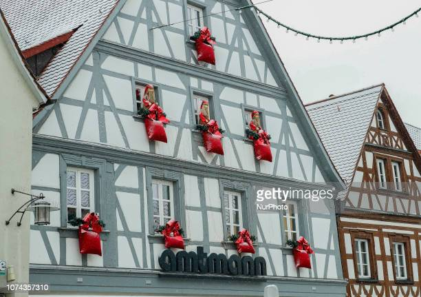 Christmas presents and Santa Claus at a wall of a shop Christmas Market in the Northern Bavarian town of Forchheim It snowed heavily but a lot of...