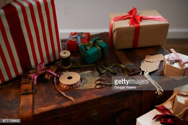 Christmas presents, ribbon and scissors on vintage suitcase.