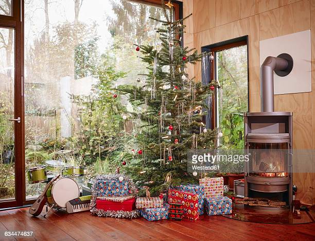 Christmas presents under Christmas tree next to cozy fireplace