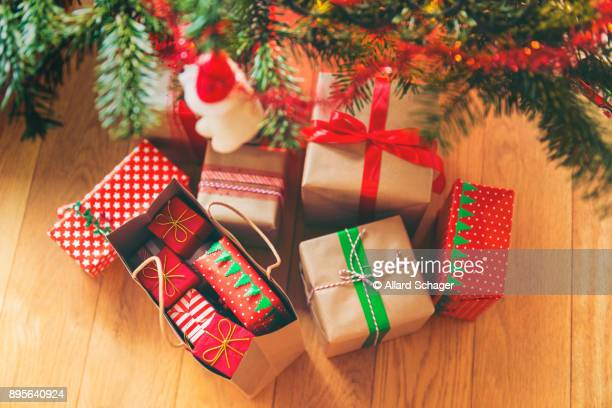 christmas presents under christmas tree - christmas gifts stock photos and pictures