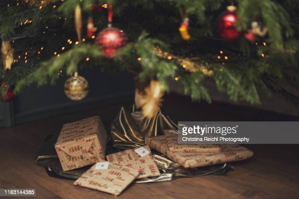 christmas presents under decorated tree - christmas trees stock pictures, royalty-free photos & images