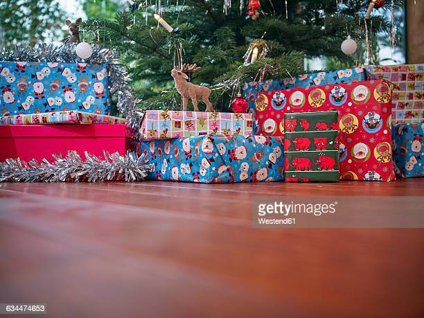 Christmas presents wrapped in colorful wrapping paper under Christmas tree