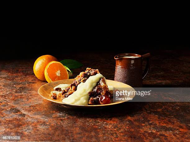 Christmas pudding with liqueur and orange sauce on gold plate, oranges, vintage pot of sauce