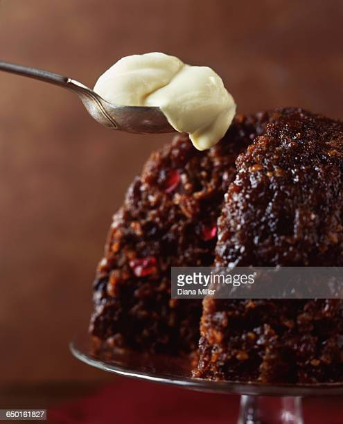 Christmas pudding with spoonful of brandy cream