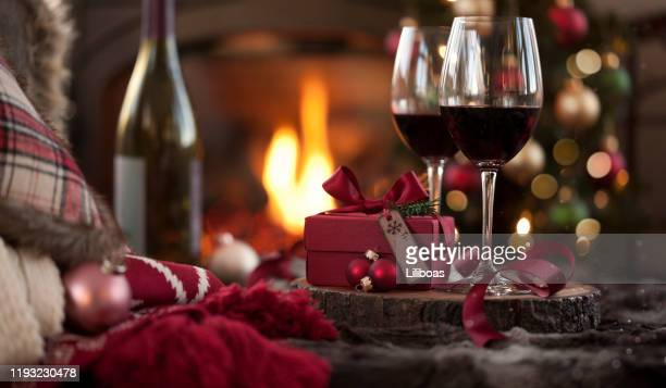 christmas red wine in front of the fireplace and christmas tree with gifts - wine stock pictures, royalty-free photos & images