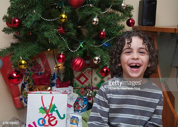 Christmas Season Happy child boy sits under the Christmas tree with Christmas gifts