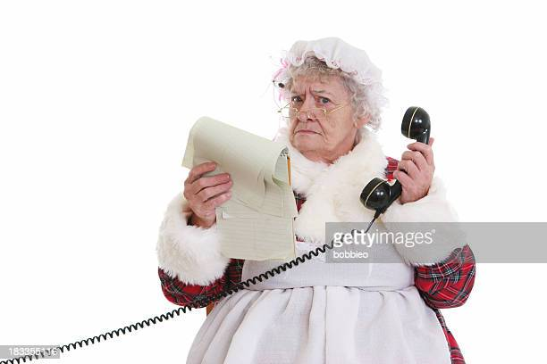 christmas: senior mrs claus with notepad and phone - naughty santa stock photos and pictures