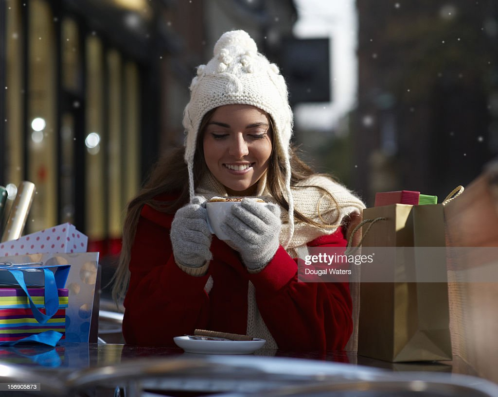 Christmas shopper holding cup of coffee. : Bildbanksbilder