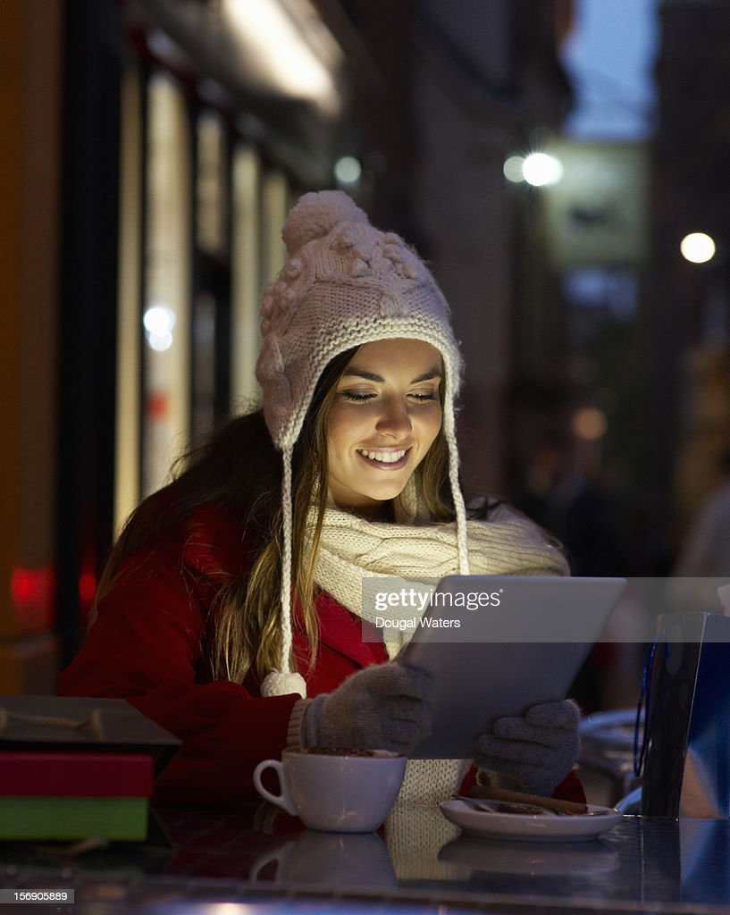 Christmas shopper using tablet at coffee shop. : Stock-Foto