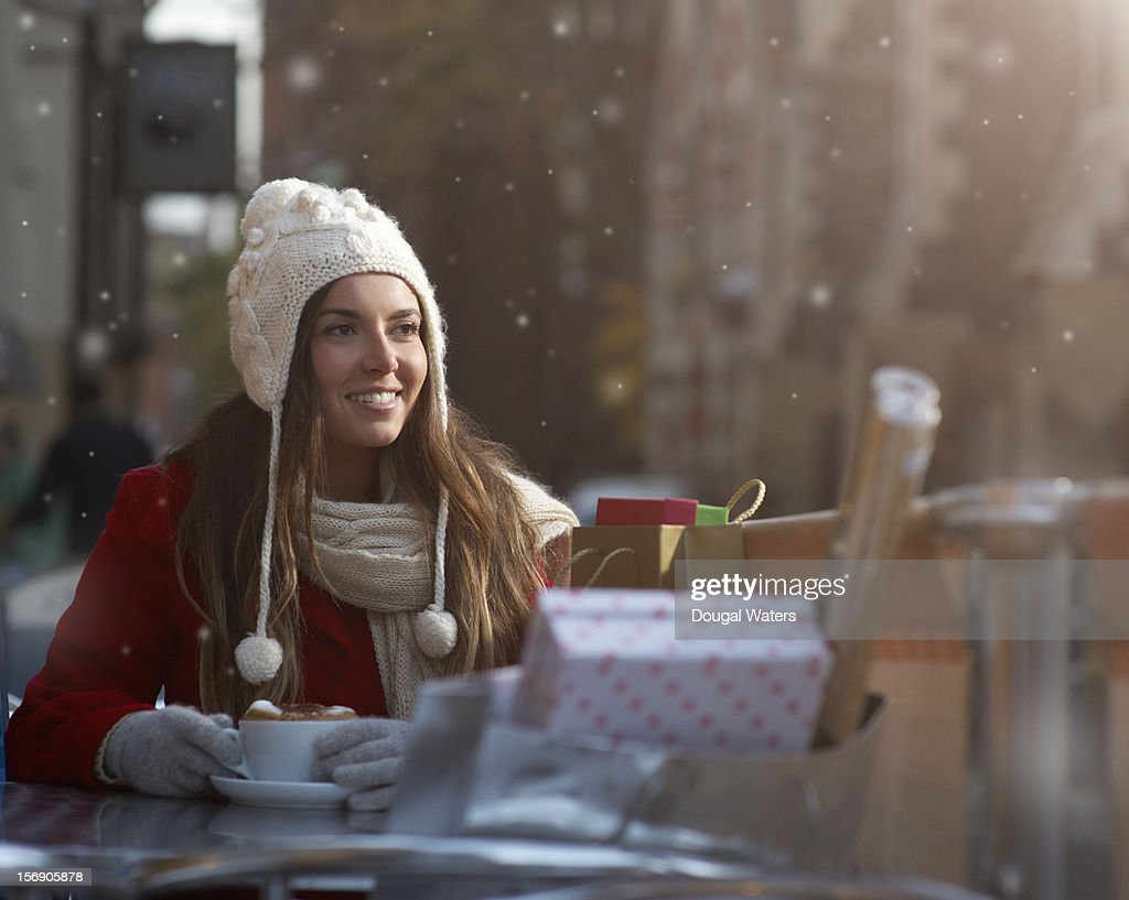 Christmas shopper with coffee and presents in snow : Stock Photo