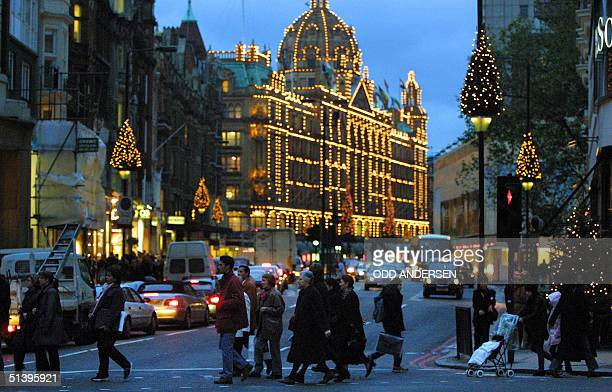 Christmas shoppers and commuters crosses Brompton road in front off an illuminated Harrods department store in Knightbridge west London, 24 November...