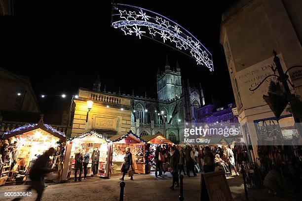 Christmas shoppers browse stalls at the traditional Christmas market close to the historic Roman Baths and Bath Abbey on December 8 2015 in Bath...