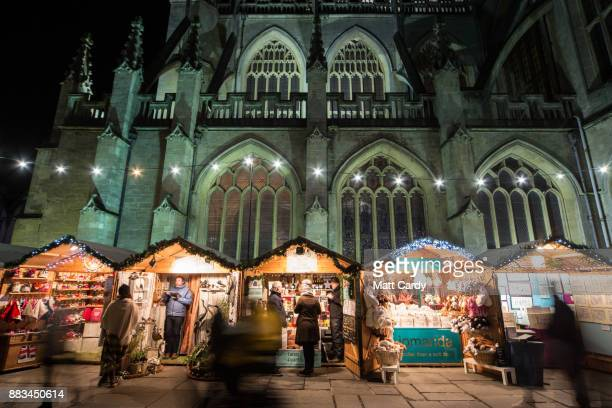 Christmas shoppers browse stalls at the traditional Christmas market that has opened close to the historic Roman Baths and Bath Abbey on November 30...