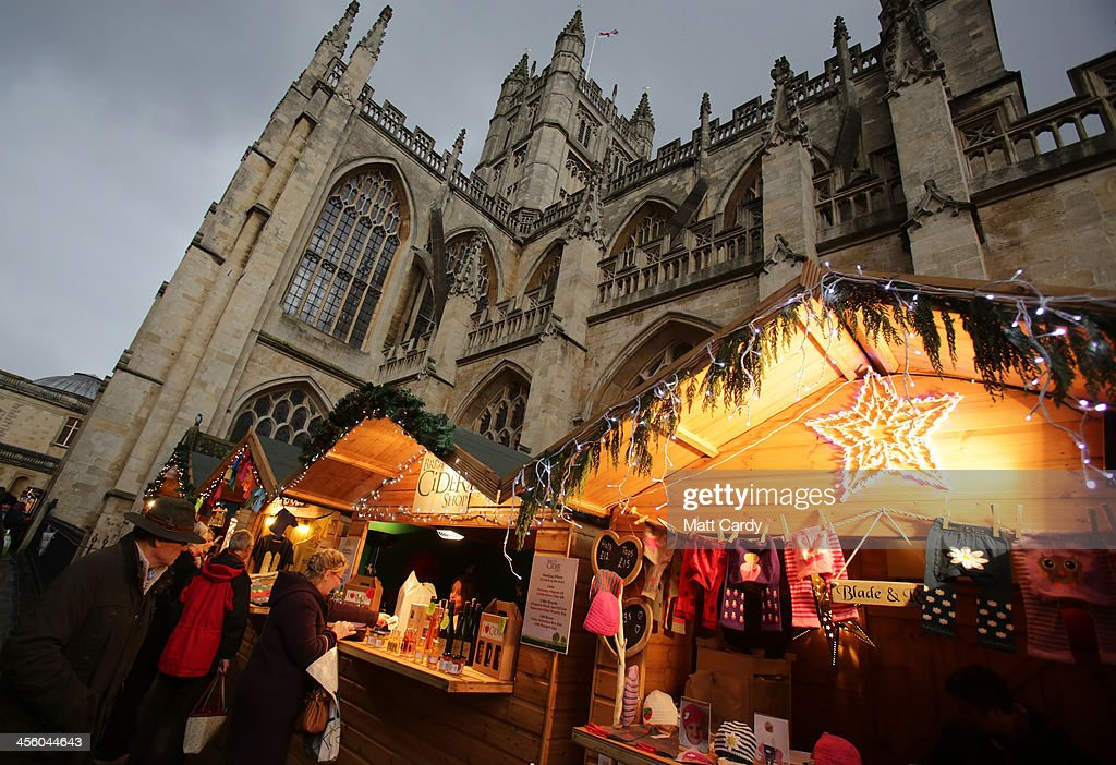 Christmas shoppers browse the stalls at the temporary Christmas Market being held in the city centre on December 13, 2013 in Bath, England. As more and more people in the UK shop online, traditional city centres such as Bath are being warned that they will need to offer much more to shoppers than they have previously to encourage visitors if they are to survive commercially in the future.