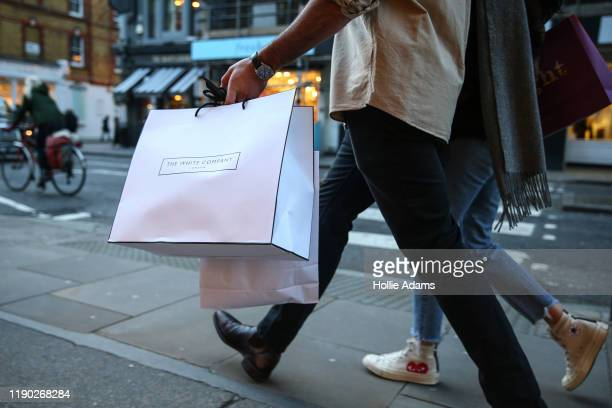 Christmas shoppers carry shopping bags on Marylebone High Street on December 23, 2019 in London, England. There are just two days left until...