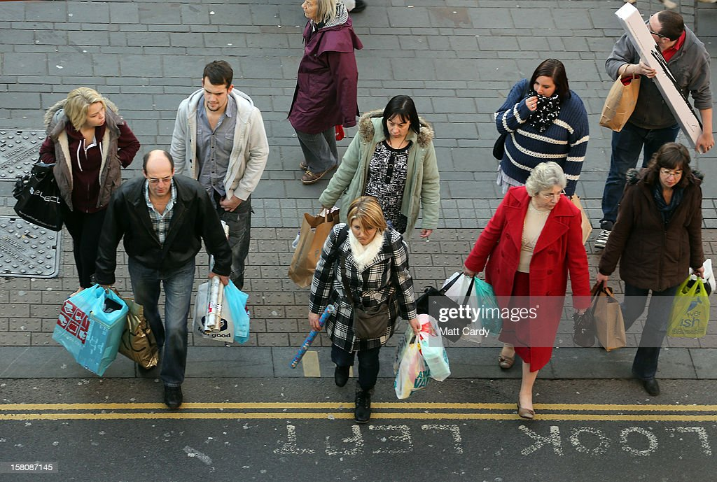 Christmas shoppers cross a road on December 10, 2012 in Bristol, England. With internet shopping still on the rise, many traditional retailers claim this Christmas could be the one that will determine the future of the high street.