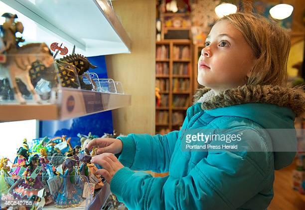 Christmas shoppers get in a last few hours of shopping on Christmas Eve in the Portland Old Port district Five year old Hatton O'Donnell looks over...