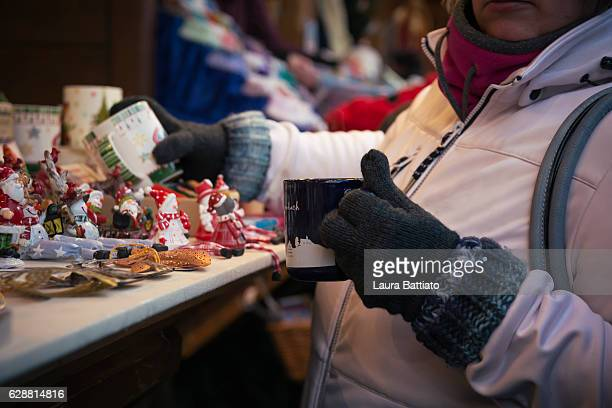Christmas Shopping - A woman is choosing ornaments in a Christmas market stall, while drinking a cup of mulled wine