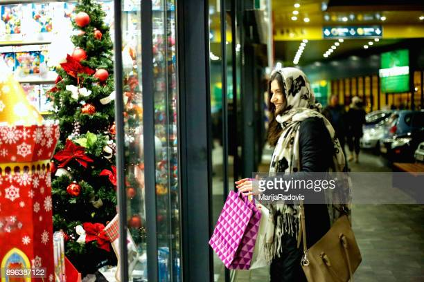 Christmas shopping bags in hand of smiling young woman