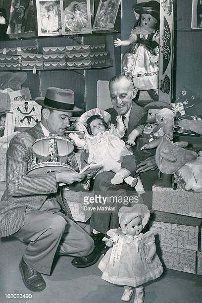 DEC 3 1951 DEC 4 1951 Christmas shopping Surrounded by beautiful women all dollsAbe Pollock president of the Denver Press club 1330 Glenarm place...