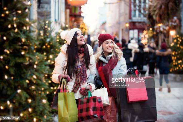 christmas shopping with two young women - buying stock pictures, royalty-free photos & images