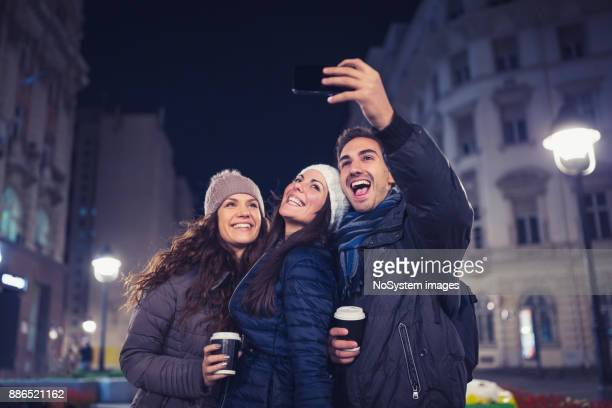 Christmas Shopping. Young people having fun outdoors, taking selfie