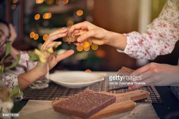 christmas. sisters sharing a chocolate nougat next to the christmas tree - kin in de hand stock pictures, royalty-free photos & images