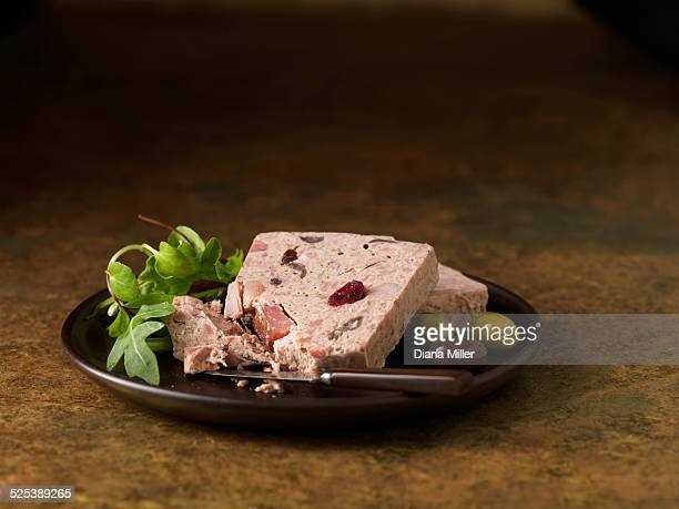 Christmas snack of smoked ham turkey & chicken terrine with cranberries. Rocket mixed salad leaves with green and black olives