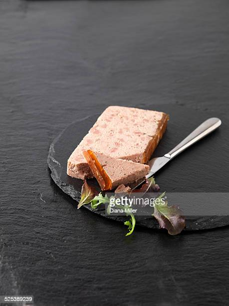 Christmas snack with Ardennes pate and rocket mixed salad leaves on slate cutting board